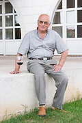 Veselko Sivric, owner and wine maker, outside his winery with a glass of wine. Podrum Vinoteka Sivric winery, Citluk, near Mostar. Federation Bosne i Hercegovine. Bosnia Herzegovina, Europe.