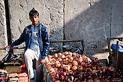 A boy sells pomegranates and pasta next to blast walls that protect the Shourjah Market in Baghdad from suicide bombers.