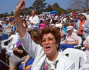 A Pilgrim Holds a Rosary Aloft During Nancy Fowler's Message from Mary.<br /> From October 13, 1990, through October 13, 1998, Conyers, Georgia housewife Nancy Fowler claimed that the Virgin Mary appeared to her and relayed messages to all citizens of the United States. The messages ranged from admonitions to prayers to warnings of war. The Virgin's supposed visits to Conyers, a suburban community about thirty miles east of Atlanta, make Conyers one of the longest-lived Marian apparition sites in the nation.<br /> In the early 1990s the roads to Conyers were clogged with pilgrims yearning to hear Mary's message. They came from every direction, but most were from heavily Hispanic southern Florida. They headed toward a large field adjacent to Fowler's home. Once there, they prayed on Mary's Holy Hill, filled bottles with water from the Blessed Well, or visited the small bookstore on the property.<br /> At midday the pilgrims moved toward Fowler's farmhouse. Inside, Fowler waited for a message from the Virgin Mary in the Apparition Room; outside, members of Our Loving Mother's Children, the volunteer group that organized the Conyers gatherings, led the crowd in song and in prayer. The pilgrims prayed in their native tongues, including English, Spanish, Russian, and Chinese. When Mary's message was broadcast over loudspeakers, the pilgrims raised their rosaries, icons, and petitions heavenward, hoping the items would be blessed by the presence of the Virgin Mary. Some claimed miracles at this site—rosaries turning to gold, the sun spinning and changing colors, and the scent of rose petals filling the air.