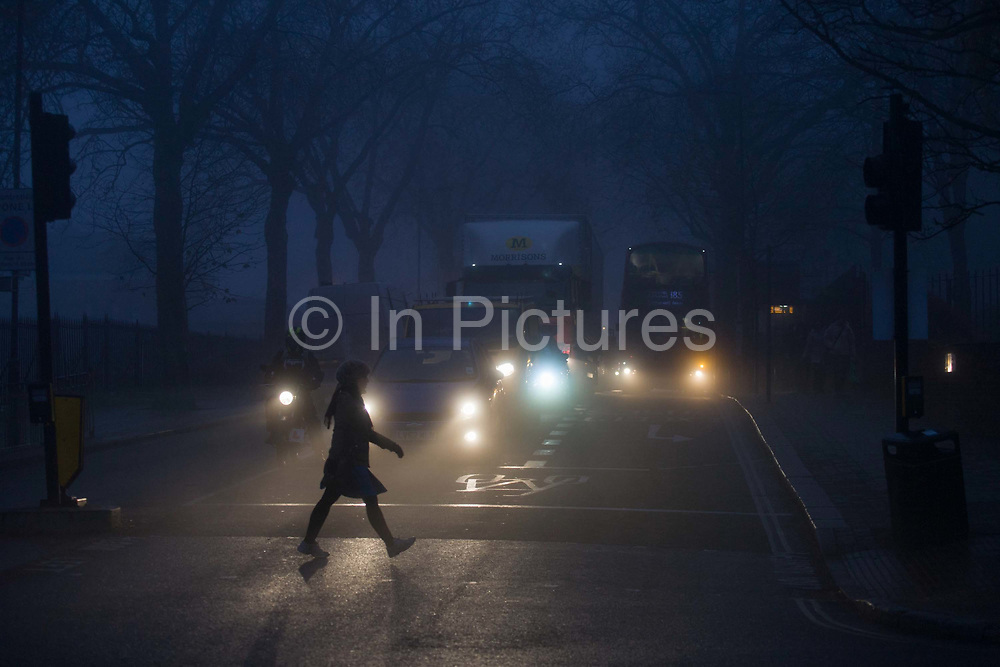 A pedestrian strides across commuter traffic at dawn on a misty morning in south London. It is dawn at around 8.45 on this winter morning, a dark and miserable time of day in this south London suburb from where Londoners start their journeys north into the City. Cars and trucks wait for the lights to change, their headlights shining in the dispersing fog on Denmark Hill. Plane trees stand over the road and an approaching bus indicates to halt at the bus stop.