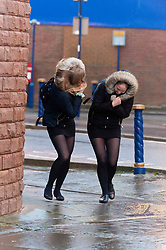 © Licensed to London News Pictures. 14/01/2020. Porthcawl, Bridgend, Wales, UK. Two young women battle against gale force winds in the small Welsh seaside resort of Porthcawl in Bridgend, UK. on the day following Storm Brendan's arrival on the south Welsh coastline, Photo credit: Graham M. Lawrence/LNP