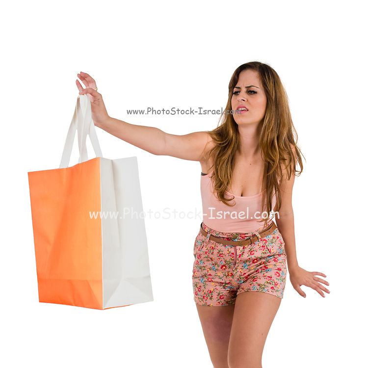 Young shopaholic woman in her twenties holds a shoping bag away from her body disgusted with her shopping habit