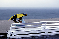 D. Ross Cameron 7/87<br /> <br /> A little girl huddles with her father under an umbrella at the boardwalk on a rainy day in Rehoboth Beach, Del.