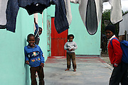 Zukiswa (middle), 8 year old girl with HIV, is standing by her home in Philippe East, an impoverished area of Cape Town.