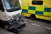 A crushed scooter lies on the road after having been knocked over by a white delivery van in central London with a passing NHS ambulance in the capital's West End. The juxtaposed ambulance and bike are merely coincidental, the ambulance having just passed-by unconnected to the incident of which there was apparently no rider or victim. Still, the damage to the bike is severe with the weight of the vehicle pressing down on the small scooter whose owner is perhaps elsewhere, soon to discover the wreck of his/her bike.