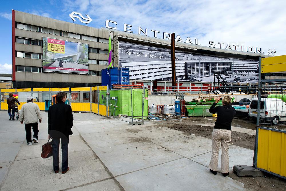 """Nederland Rotterdam 3 september 2007 20070903 ..Voorbijgangers/ reizigers fotograferen en bekijken de vertrouwde oude hal van het voormalige centraal station nog een keer voordat het definitief gesloopt zal worden.  ."""" Het doek is gevallen """" Zondag 2 september is het doek letterlijk doek gevallen voor het in 1957 geopende gebouw. Over enkele weken wordt de schepping van architect Sybold van Ravesteyn gesloopt en komt op het Stationsplein een nieuwe OV-terminal, die na 2011 ruim 300.000 reizigers per dag moet kunnen verwerken. Voorbijgangers maken een foto van het oude bekende centraal station, dat sinds 1957 dienst heeft gedaan. Een gloednieuw station zal op deze plek verrijzen. ..Het tijdelijke station dat de periode overbrugt tussen de sloop van het oude Rotterdam CS en de bouw van een nieuw station, kost 12 miljoen euro. Dat is een schijntje vergeleken met het half miljard waarop het nieuwe is begroot. De bedoeling is dat de tijdelijke bebouwing in februari klaar is. Het blijft open tot 2010. Het oude gebouw maakt plaats voor vijf tijdelijke. Daarvan zijn er vier voor de reizigers en een voor het personeel van de Spoorwegpolitie. ..Tijdelijk Rotterdam Centraal.1 september 2007..Alle treinreizigers opgelet! Vanaf 2 september sta je voor een dichte deur als je bij Rotterdam Centraal op de trein wilt stappen. Tenzij je de ingang van het tijdelijke Rotterdam Centraal al gevonden hebt. ..Naast het oude vertrouwde station staat al een tijdje een groot blauw gebouw en vanaf 2 september kun je daar op je trein stappen. Je kunt er zelfs een kopje koffie halen, of kleine boodschappen doen. Alle winkels zijn namelijk gewoon verplaatst naar het grootste tijdelijke station van Nederland...Het Centraal Station was al een hele tijd een grote bouwput, want er wordt heel hard gewerkt aan een nieuw, beter en vooral moderner station. Maar omdat afscheid nemen altijd zo moeilijk is, vindt er op 12 september een soort ode aan het station en de architect Sybold van Ravesteyn plaats. D"""