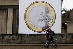 © Licensed to London News Pictures. 02/02/2017. LONDON, UK.  A couple with a black umbrella walk past the artwork 'Euro (2012)', by the Danish artists Superflex, as it hangs on the wall of the South Bank Centre during rain and wet weather today. The artwork will be on display in London until the end of February.  MP's last night voted in Parliament to back the 'Brexit Bill' and trigger Article 50, to begin the formal Brexit process for the United Kingdom leaving the European Union.  Photo credit: Vickie Flores/LNP