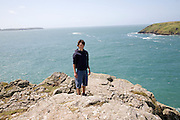 Model released picture of teenage boy standing on a cliff being blown by strong wind in Pembrokeshire, Wales, UK