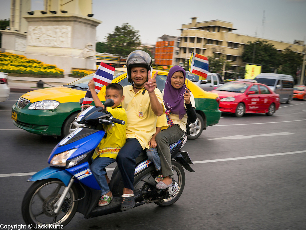 05 DECEMBER 2012 - BANGKOK, THAILAND: A Muslim family dressed in yellow, the color of the Thai King, rides through old Bangkok on the motor scooter during the public ceremony to celebrate the birthday of Bhumibol Adulyadej, the King of Thailand, on Sanam Luang, a vast public space in front of the Grand Palace in Bangkok Wednesday night. The King celebrated his 85th birthday Wednesday and hundreds of thousands of Thais attended the day long celebration around the Grand Palace and the Royal Plaza, north of the Palace. The Thai monarch is revered by most Thais as unifying force in Thailand's society, which is not yet recovered from the political violence of 2010.      PHOTO BY JACK KURTZ