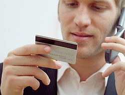 Dec. 14, 2012 - Man on mobile with credit card (Credit Image: © Image Source/ZUMAPRESS.com)
