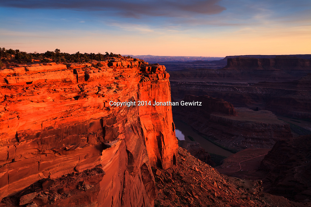 Warm light from the setting sun highlights Dead Horse Point over the Colorado River near Moab, Utah. WATERMARKS WILL NOT APPEAR ON PRINTS OR LICENSED IMAGES.<br /> <br /> Licensing: https://tandemstock.com/assets/74637687