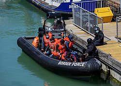 © Licensed to London News Pictures. 18/07/2021. Dover, UK. Migrants are brought ashore by a Border Force officer at Dover Harbour in Kent after crossing the English Channel. Photo credit: Stuart Brock/LNP