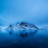 Heavy clouds conceal summit of Olstind mountain peak rising from fjord, Reine, Moskenesøy, Lofoten Islands, Norway