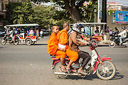 30 JANUARY 2013 - PHNOM PENH, CAMBODIA:  Buddhist monks on a motorcycle taxi in Phnom Penh, Cambodia. Motorcycles are used as informal taxis in much of Southeast Asia.    PHOTO BY JACK KURTZ