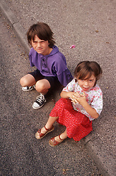 Two young children sitting outside on pavement,