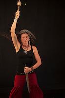 Shamanic priestess with prayer wheel and a symbolic dagger cutting through negative energy.