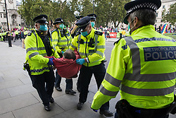 London, UK. 1st September, 2020. Metropolitan Police officers arrest a climate activist from Extinction Rebellion who had occupied a road around Parliament Square during a Back The Bill rally. Extinction Rebellion activists are attending a series of September Rebellion protests around the UK to call on politicians to back the Climate and Ecological Emergency Bill (CEE Bill) which requires, among other measures, a serious plan to deal with the UK's share of emissions and to halt critical rises in global temperatures and for ordinary people to be involved in future environmental planning by means of a Citizens' Assembly.