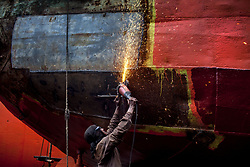 August 2, 2017 - Dhaka, Dhaka, Bangladesh - August 02, 2017 Dhaka, Bangladesh – A Labour weldingt ship in a dockyard in the side of Buriganga River. The laborers work in the dockyard without proper safety measures and unsafe conditions. Mostly the Local Ships are built and repair in this place. Ship repair, Sewage from the city, oil spills from boats and chemicals from industry have all led to pollution in the Burigonga River. (Credit Image: © K M Asad via ZUMA Wire)