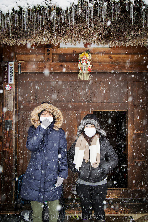 Two women sheltering from snow under roof, Shirakawa-go, Japan
