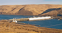 John Day Dam on the Columbia River between Washington and Oregon, USA, with a wind farm atop the ridge across the river on the Oregon side  of the river.