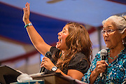 """13 JULY 2012 - FT DEFIANCE, AZ: Members of the Navajo gospel group """"Fruitland Trio"""" sing at the 23rd annual Navajo Nation Camp Meeting in Ft. Defiance, north of Window Rock, AZ, on the Navajo reservation. Preachers from across the Navajo Nation, and the western US, come to Navajo Nation Camp Meeting to preach an evangelical form of Christianity. Evangelical Christians make up a growing part of the reservation - there are now more than a hundred camp meetings and tent revivals on the reservation every year. The camp meeting in Ft. Defiance draws nearly 200 people each night of its six day run. Many of the attendees convert to evangelical Christianity from traditional Navajo beliefs, Catholicism or Mormonism. """"Camp meetings"""" are a form of Protestant Christian religious services originating in Britain and once common in rural parts of the United States. People would travel a great distance to a particular site to camp out, listen to itinerant preachers, and pray. This suited the rural life, before cars and highways were common, because rural areas often lacked traditional churches. PHOTO BY JACK KURTZ"""
