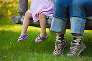 Mother and daughter sit together on a bench swing on a farm in Chugiak, Alaska.