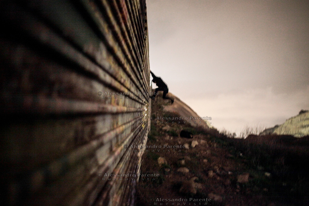 Migrant from Honduras run and jump at the fence to climb it .