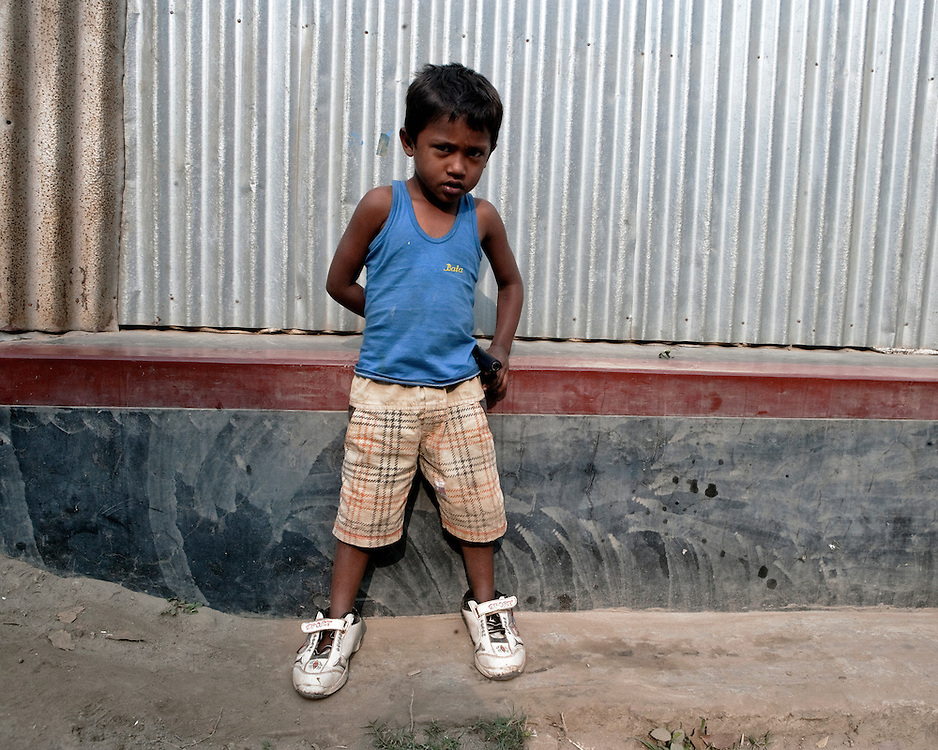 Portrait of a boy playing on the street corner in Asia with a toy gun