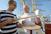 A rigger of Royal Clipper prepares the model of a Vikings' navigation tool for a demonstration by Captain Klaus.
