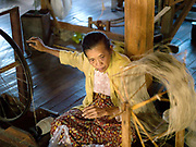 An elderly woman spins lotus plant fibre at In Paw Khone, a village of stilt houses on Inle Lake, Shan State, Myanmar (Burma). The thread will be used for making woven textiles out of a combination of lotus plant fibres and silk.  Lotus textiles are one of the most expensive textiles in the world. After picking, the fibres are extracted by pulling out, twisting and handrolling together with water and then spun, washed and woven into fabric, an extremely labour intensive process.
