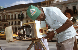 Photographer using ancient handmade camera to photograph people on the steps of the Capitolio; Havana; Cuba, He uses paper for the negative and rephotographs it to make the positive print,