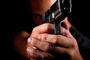 Man holds hand gun pointed at viewer - model rellease available