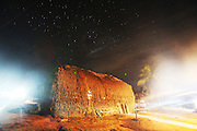 Night time: A traditional thatched Surui house that hasn't changed design for several generations or hundreds of years<br /><br />An Amazonian tribal chief Almir Narayamogo, leader of 1350 Surui Indians in Rondônia, near Cacaol, Brazil, with a $100,000 bounty on his head, is fighting for the survival of his people and their forest, and using the world's modern hi-tech tools; computers, smartphones, Google Earth and digital forestry surveillance. So far their fight has been very effective, leading to a most promising and novel result. In 2013, Almir Narayamogo, led his people to be the first and unique indigenous tribe in the world to manage their own REDD+ carbon project and sell carbon credits to the industrial world. By marketing the CO2 capacity of 250 000 hectares of their virgin forest, the forty year old Surui, has ensured the preservation, as well as a future of his community. <br /><br />In 2009, the four clans and 25 Surui villages voted in favour of a total moratorium on logging and the carbon credits project. <br /><br />They still face deforestation problems, such as illegal logging, and gold mining which causes pollution of their river systems