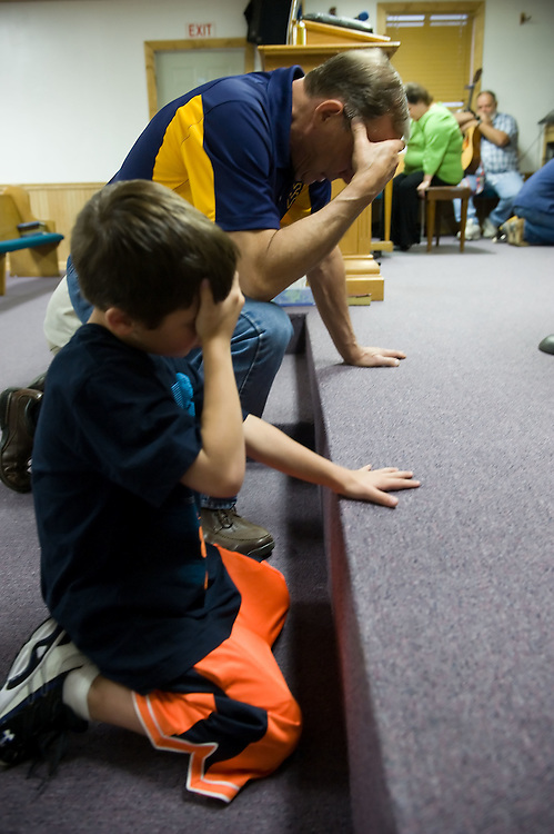 Nathan Ramsey, 7, foreground, and Jerry Ramsey, center, pray for the fallen miners and their families during a church service at Stepping Stone Community Church in Tolleystown, WV on Wednesday, April 7, 2010.  The community gathered across Raleigh and Boone Counties to pray and remember the victims and their families.