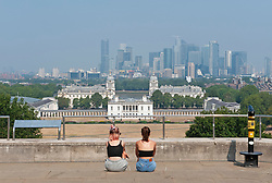 ©Licensed to London News Pictures 12/08/2020             Greenwich, UK. Two young women sitting on steps looking towards the Queen's House. The hot heatwave weather continues in London and the South East today with people out and about in Greenwich park, London. Photo credit: Grant Falvey/LNP