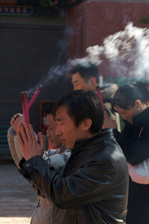 Incense flys as people kneel and bow at Yonghegong a Tibetan Buddhist Temple, also called the Lama Temple in northern Beijing,China.