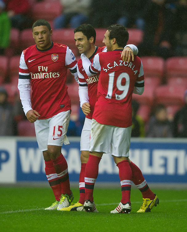 Arsenal's Mikel Arteta celebrates scoring the only goal of the match from the penalty spot with team-mates Santi Cazorla (R) and Alex Oxlade-Chamberlain (L)..Football - Barclays Premiership - Wigan Athletic v Arsenal - Saturday 22nd December 2012 - DW Stadium - Wigan..
