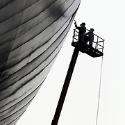 two workers on the side of a ship supported by a spraying platform
