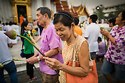 "25 FEBRUARY 2013 - BANGKOK, THAILAND:  People participate in a procession around Wat Benchamabophit Dusitvanaram (popularly known as either Wat Bencha or the Marble Temple) on Makha Bucha Day. Thais visit temples throughout the Kingdom on Makha Bucha Day to make merit and participate in candle light processions around the temples. Makha Bucha is a Buddhist holiday celebrated in Myanmar (Burma), Thailand, Cambodia and Laos on the full moon day of the third lunar month (February 25 in 2013). The third lunar month is known in Thai is Makha. Bucha is a Thai word meaning ""to venerate"" or ""to honor"". Makha Bucha Day is for the veneration of Buddha and his teachings on the full moon day of the third lunar month. Makha Bucha Day marks the day that 1,250 Arahata spontaneously came to see the Buddha. The Buddha in turn laid down the principles his teachings. In Thailand, this teaching has been dubbed the 'Heart of Buddhism'.     PHOTO BY JACK KURTZ"