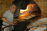 Israel, Jaffa, Baking pita in a stone oven