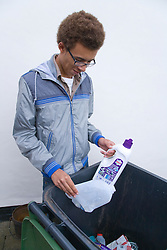 Teenage boy putting plastic containers into recycling wheelie bin ready for collection,