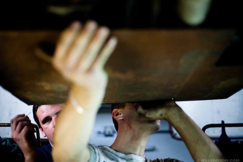 Russian-speaking mechanics attach a piece of scrap metal to the undercarriage of Team Great Job's Nissan Micra in Lodz, Poland. The metal would protect the car from scrapes and punctures on the mostly unpaved roads of Mongolia.