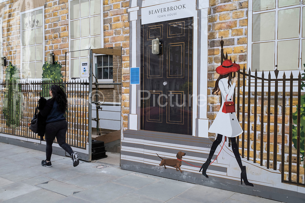 High end real estate under redevelopment covered with a hoarding depicting a fashionable woman out walking her dog past a finished home with large windows on Sloane Street in the upmarket area of Chelsea on 14th April 2021 in London, United Kingdom. Chelsea is one of the principal areas for exclusive, luxury goods in West London. It is known as a district where the rich and wealthy shop, mostly for high end fashion and jewellery.