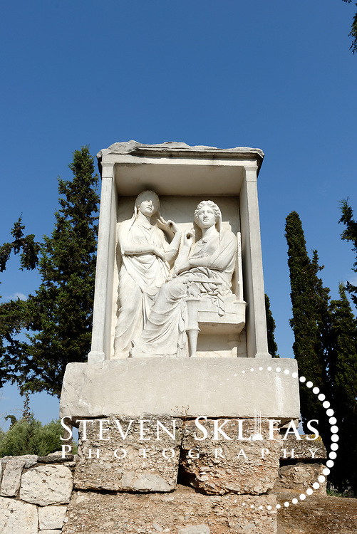 Grave relief of two sisters Demetria and Pamphile, dating from 325-310BC. Kerameikos. Athens. Greece. The stele or relief sculpture which is a copy (original is in the museum) is located on the Street of the Tombs, which is the excavated part of the ancient main road to Piraeus. Serving as a burial ground as long ago as the 12th century BC, Kerameikos located in the ancient neighbourhood of potters contains part of the ancient city walls and the Dipylon, the main gate of Ancient Athens at a junction of the Sacred Way and Panathenaic Way. It served as a burial ground for the richest and most distinguished citizens of the city.
