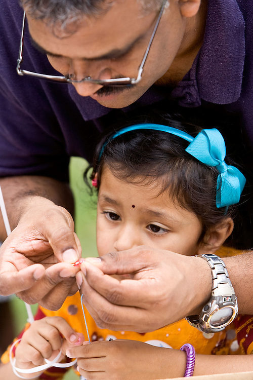 NAUGATUCK, CT - 23 AUGUST 2009 -082309JT02-.Jay Chan of Naugatuck helps his daughter Divya, 3, make a bead necklace at a station at Naugatuck's annual back-to-school fair at the green on Sunday. The event also featured a backpack drop-off to donate to needy families in Naugatuck..Josalee Thrift Republican-American