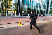One of three members of the Extinction Rebellion environmental activist group is seen rushing towards Barclays HQ building in Canary Wharf to spray it with a dark colour on Thursday, May 7, 2020. Barclays is the biggest European financier of fossil fuel companies. (Photo/ Vudi Xhymshiti)