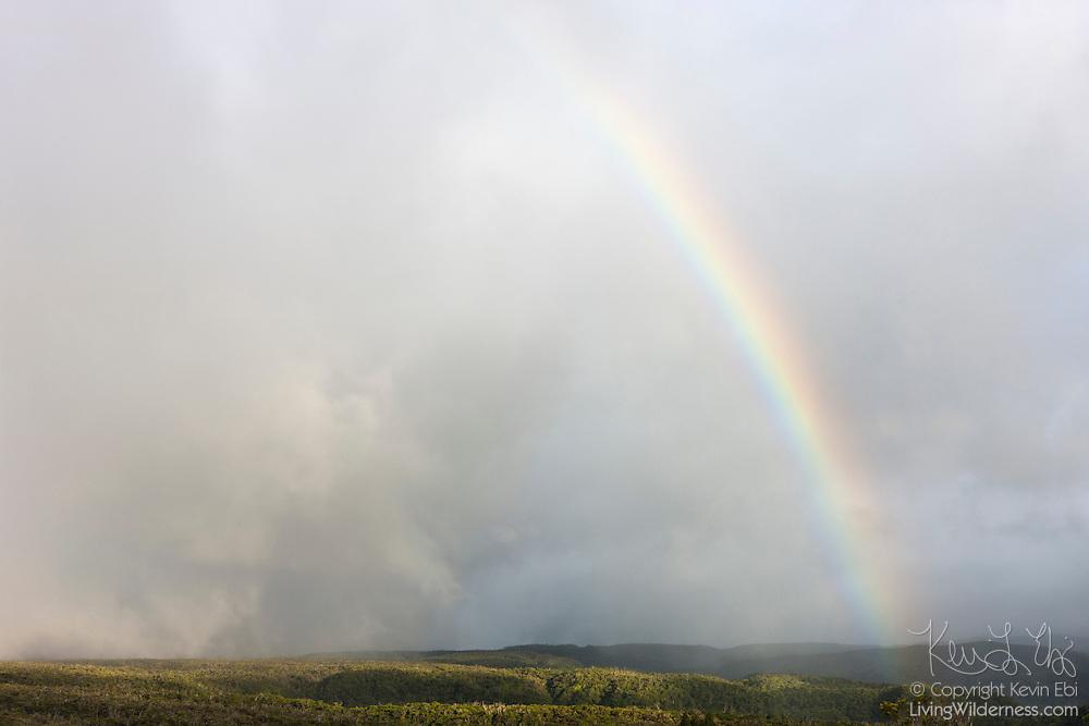 A large, bright rainbow forms during a rainstorm over the Kalalau Valley on the island of Kauai, Hawaii.