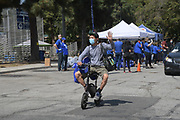 A motorist arrives at Dodger Day Drive-Thru at Belvedere Park, Tuesday, June 30, 2020, in Los Angeles. The event was hosted by The Los Angeles Dodgers Foundation, which distributed food boxes, books, sports equipment, clothing, toys and hygiene supplies to more than 1,000 registered youth from the Boyle Heights, East Los Angeles, La Puente and Monterey Park communities.