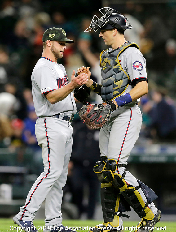 Minnesota Twins closing pitcher Austin Adams and catcher Jason Castro greet each other after the 18-4 win over the Seattle Mariners in a baseball game, Saturday, May 18, 2019, in Seattle. (AP Photo/John Froschauer)