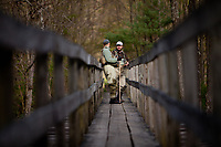 Male fly anglers surveying the water from a foot bridge over Penn's Creek in Pennsylvania.